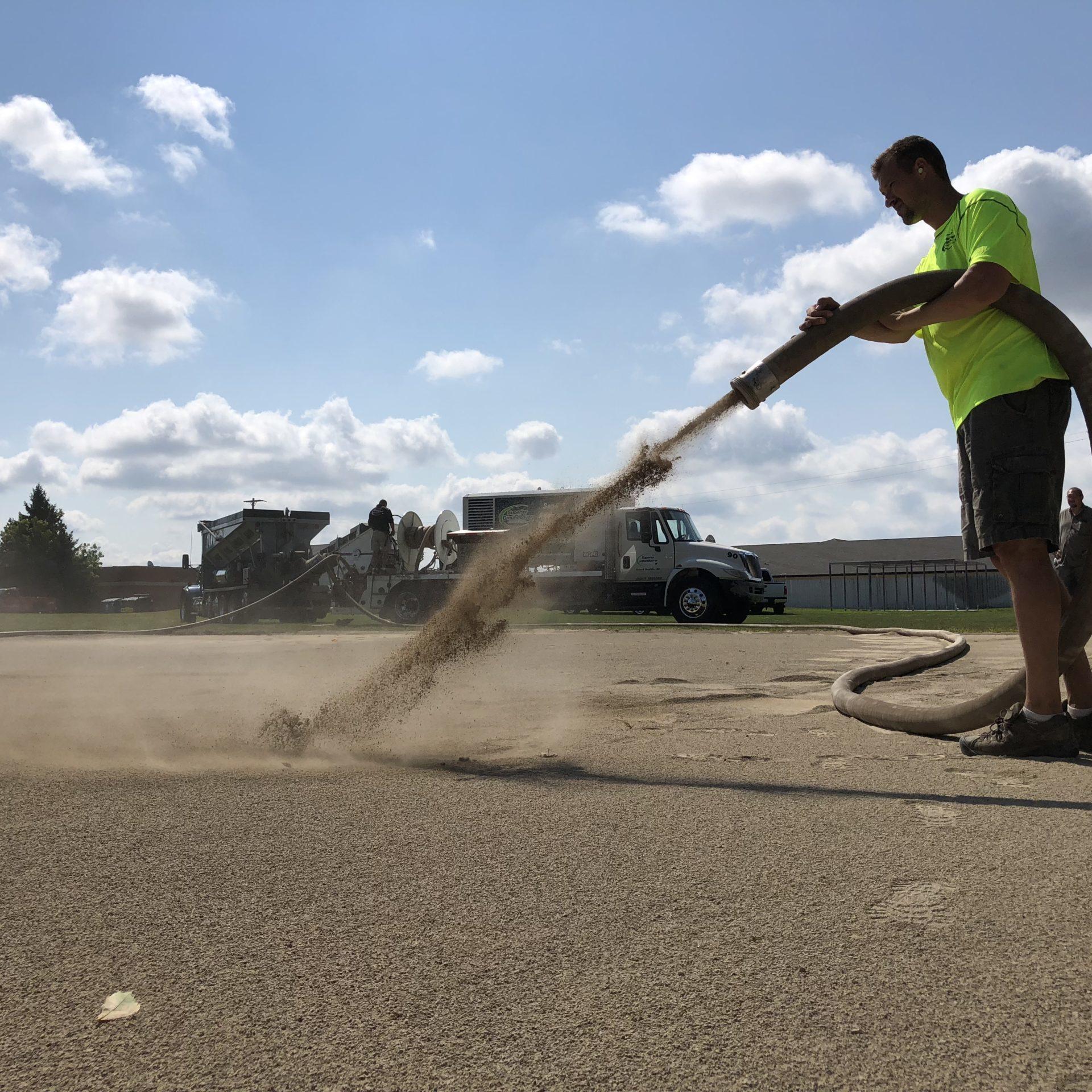 Stone blower truck installing chips n dust for a baseball field