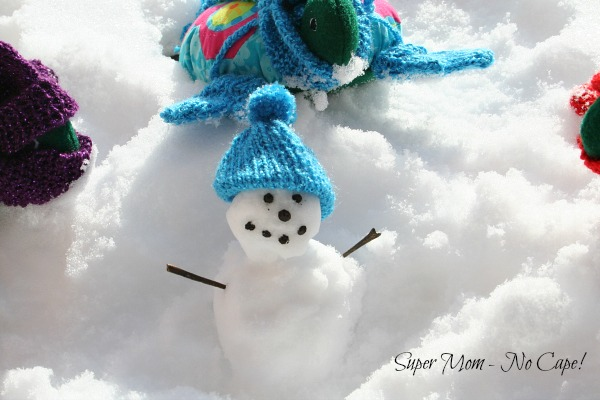 Miniature snowman wearing Lexie's knitted hat.