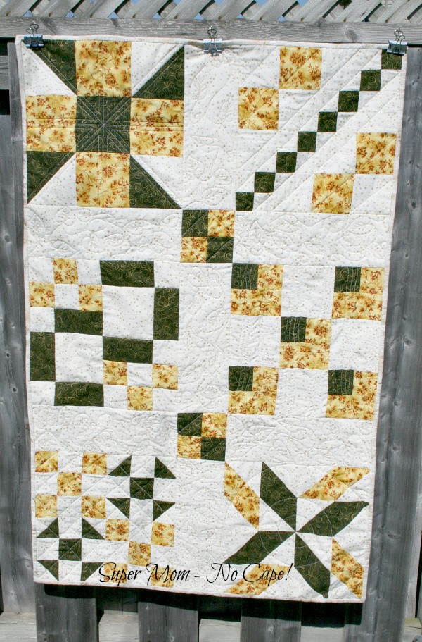 Sampler Table Runner hanging on the fence