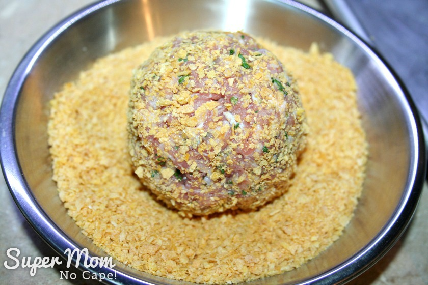 Gluten Free Baked Scotch Eggs - place meat covered egg in beaten egg mixture - roll scotch egg in crushed corn flakes