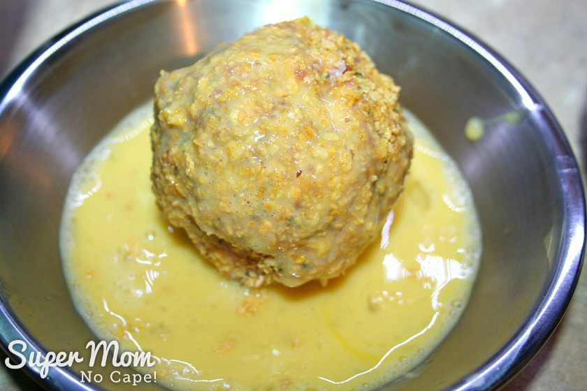Gluten Free Baked Scotch Eggs - returned coated scotch egg to egg mixture