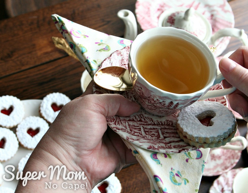 Photo of a cup of tea with gold spoon and a Snow Storm Linzer Cookie with the tea table in the background