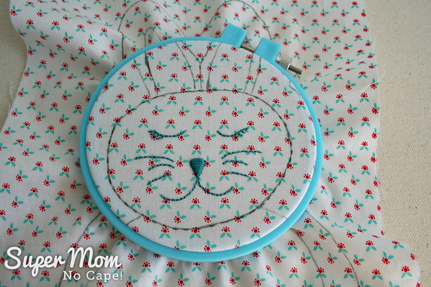 Photo of the embroidered face of the rag quilt bunny inside a small blue embroidery frame