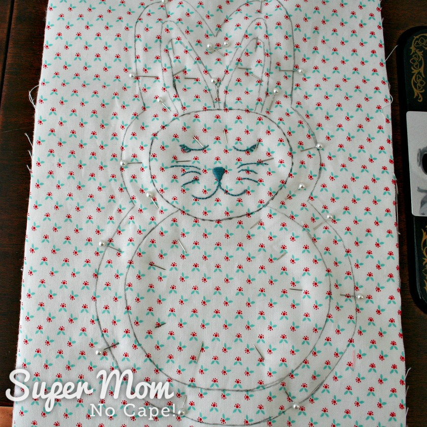 Photo of the traced bunny pinned to the layers of the batting and backing fabric
