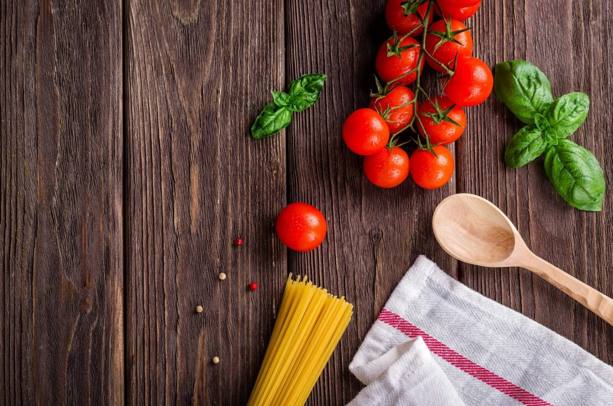 dark stained wood background with cherry tomatoes, uncooked spaghetti noodles, a white towel with a red stripe, a wooden spoon and basil leaves on it