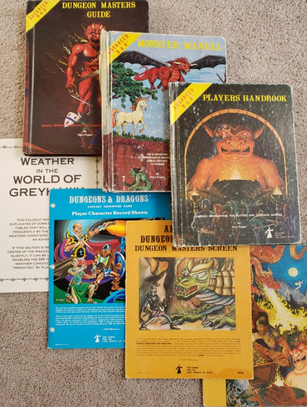 A collection of vintage D&D rulebooks, along with a dungeon master's screen and a few peripherals