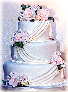 Picture of Three tier white wedding cake with pink roses