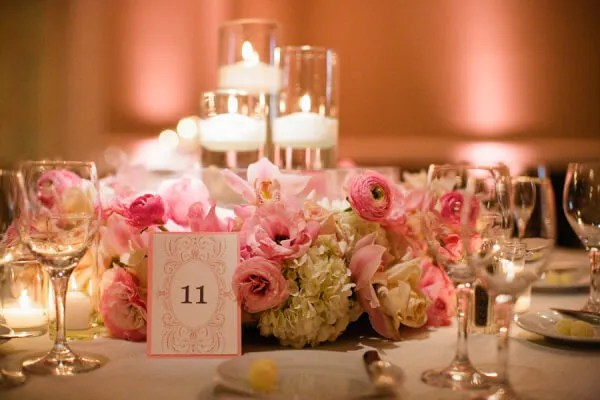Floral wreath wedding centerpieces with floating candles in cylinder vases.