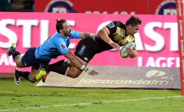 Bjorn Basson of the Bulls can't stop Rohan Janse van Rensburg of the Lions f