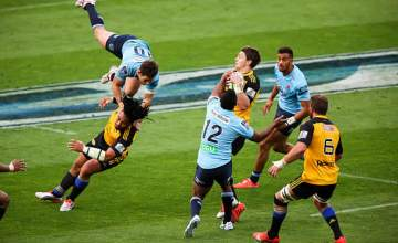 Beauden Barrett catches the ball as Bernard Foley jumps for a high ball