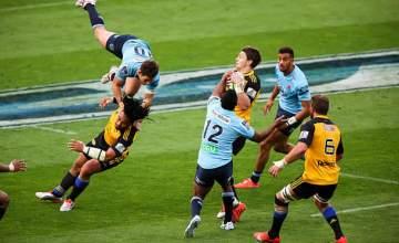 Beauden Barrett catches the ball as Bernard Foley jumps for a high ball