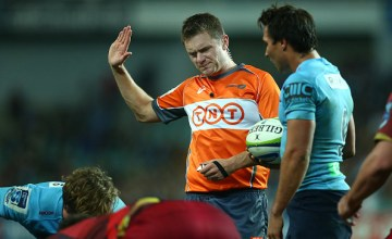 Referee Nick Briant officiates at a scrum between the Waratahs and the Reds