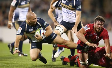 Robbie Abel of the Brumbies is tackled by Kane Douglas of the Reds