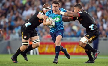 Bryn Gatland of the Blues looks to fend off the tackles from the Chiefs during the round two Super Rugby match between the Blues and the Chiefs