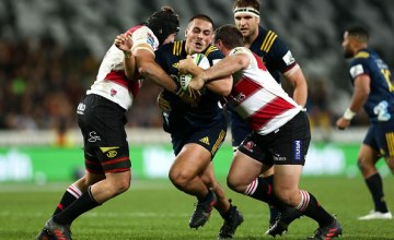 Daniel Lienert-Brown of the Highlanders is tackled by Dylan Smith and Cyle Brink of the Lions during the round 12 Super Rugby match