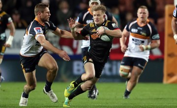 Chiefs Damian McKenzie looks to fend off the tackle during the round 18 Super Rugby match between the Chiefs and the Brumbies at FMG Stadium Waikato