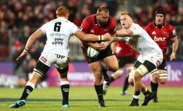Joe Moody of the Crusaders is tackled by Jean-Luc du Preez and Philip van der Walt of the Sharks during the round 12 Super Rugby match between the Crusaders and Sharks at Christchurch Stadium