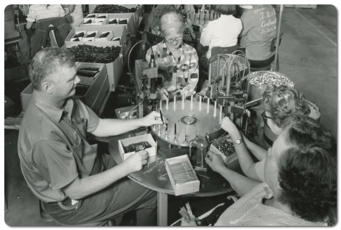 Historical black and white photo. Three women and a man are gathered around a circular table, assembling SKILCRAFT pens together.