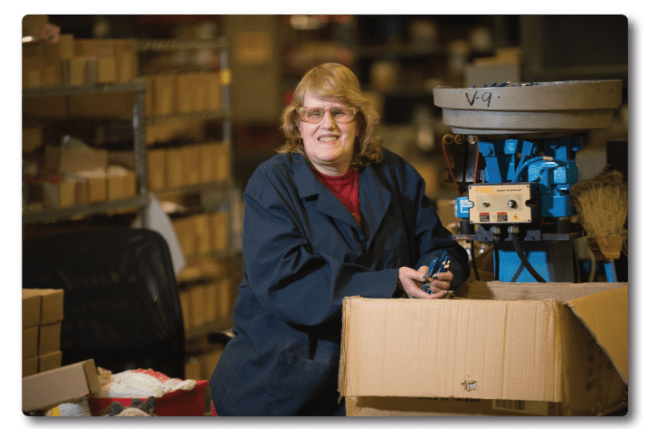 Susan from IBVI smiles and stands beside a large cardboard box, with machinery behind her. She's holding over a dozen SKILCRAFT pens in both her hands.