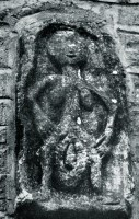 stone relief of woman holding huge vulva, on church wall archived by Max Dashu