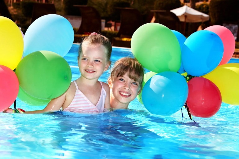 girls in pool with balloons