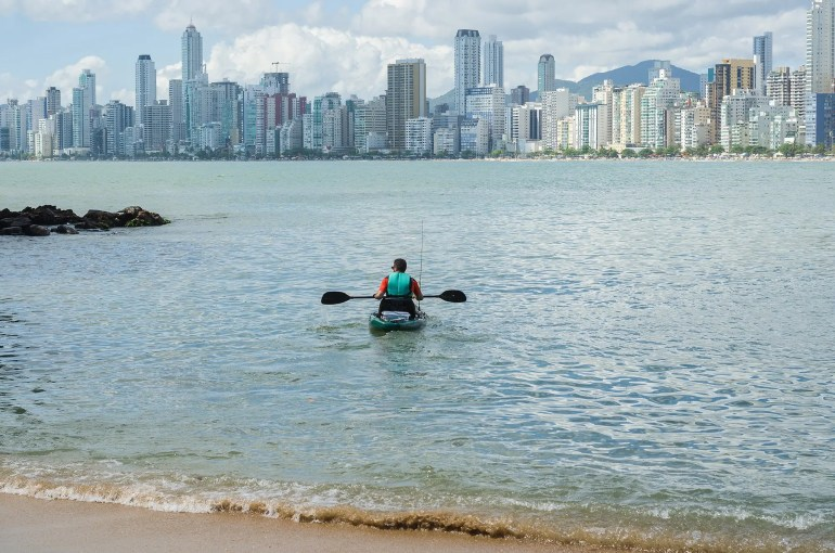Kayaker in front of big city