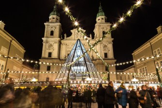 Salzburg, Austria - December 11, 2015: Decorations and buildings at Salzburg Christmas Market in the Domplatz area at night. People can be seen.