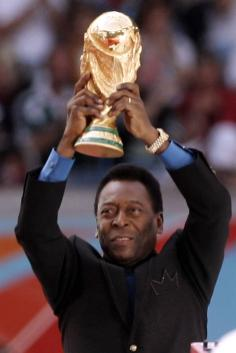 Pele of Brasil lifts up the World Cup Trophy