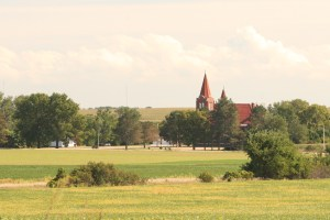 fields with church steeple in background