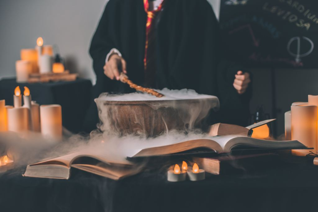 steaming cauldron with hand holding wand above it