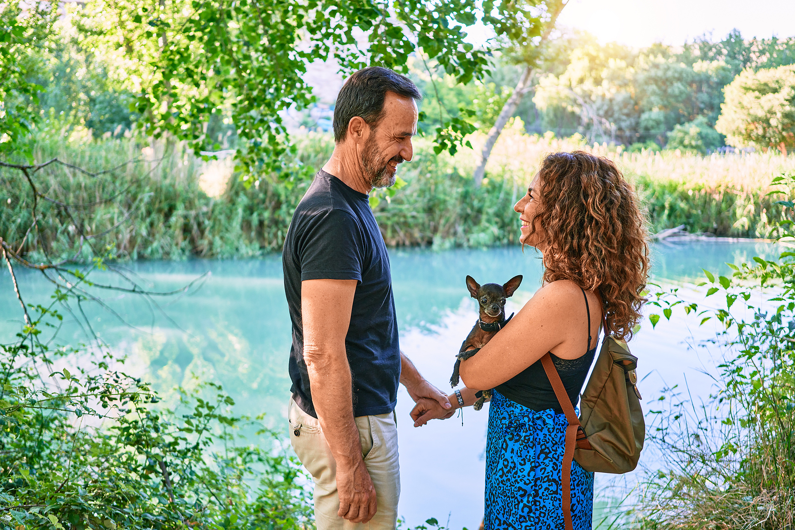 Middle age couple wearing casual clothes standing around river holding chihuahua dog at the park