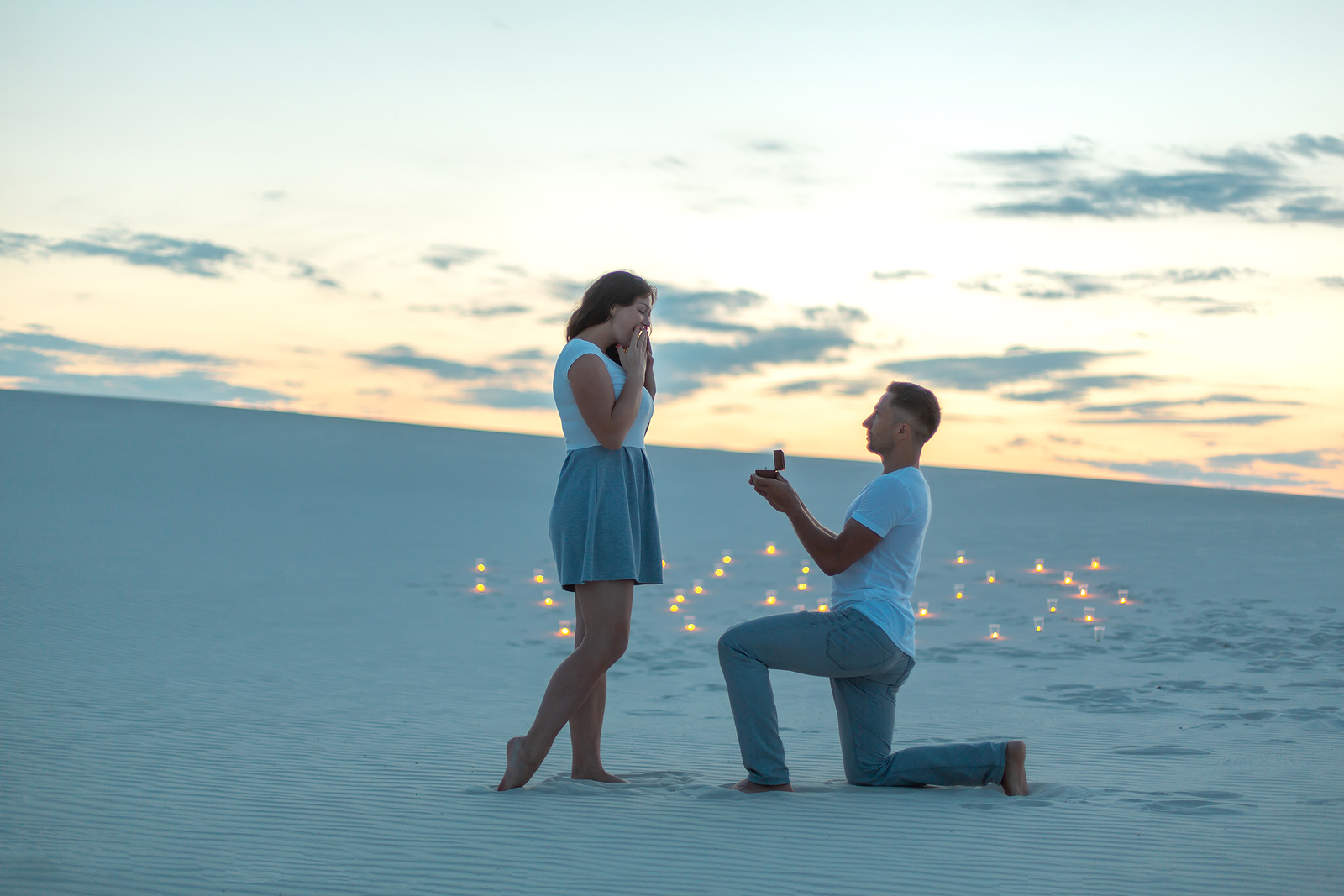 The guy makes the girl a marriage proposal by bending his knee while standing on the sand in the desert. Evening, candles burn in the sand