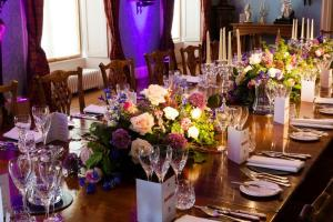 dining table laid with flowers, water jugs and cutlery