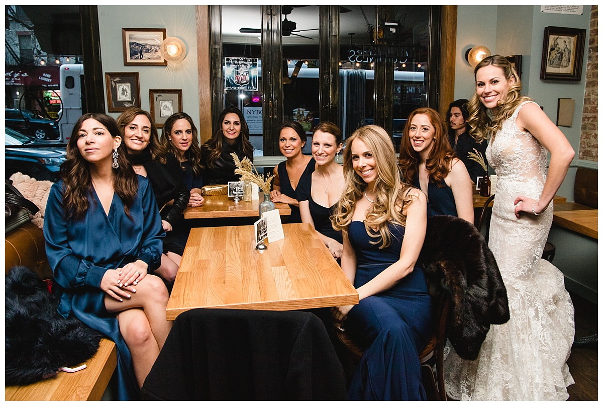 A bride and her bridesmaids hanging out at a bar on a wedding day at Guastavinos in New York City. Dress by Ines Di Santo.