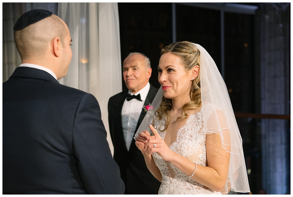 A bride and a groom exchanging their wedding ring during a jewish wedding ceremony at Guastavinos in New York City. Dress by Ines Di Santo.
