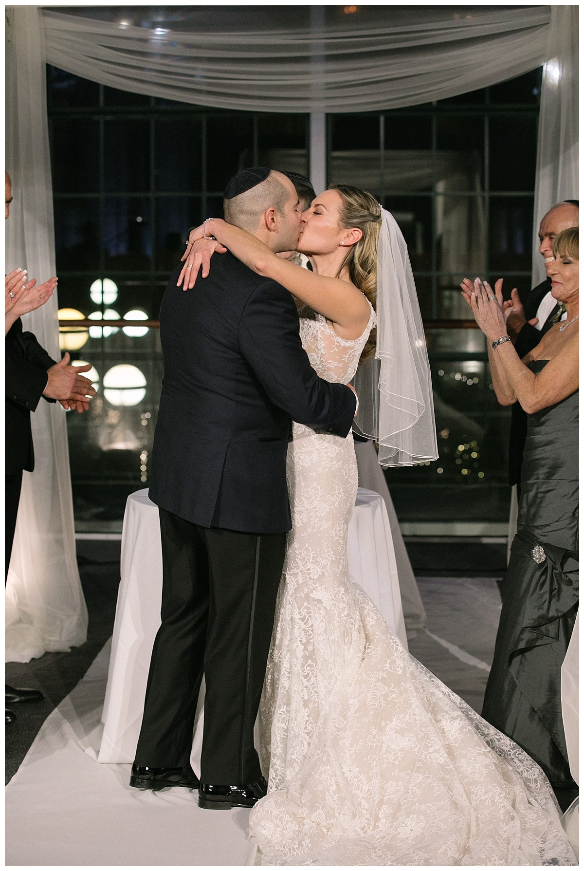 A bride and a groom kissing during a jewish wedding ceremony at Guastavinos in New York City. Dress by Ines Di Santo.