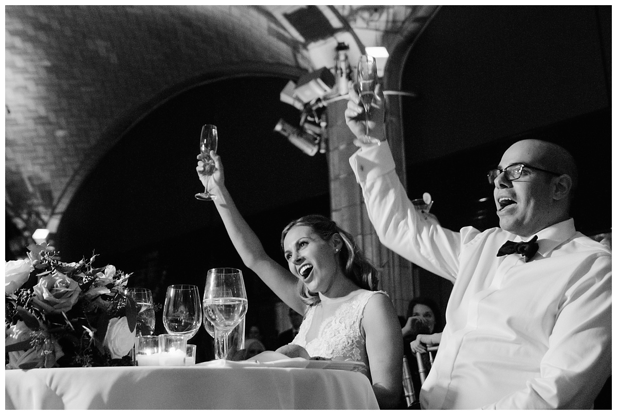 A newly wedded couple raising their glasses during a wedding reception at Guastavinos in New York City.