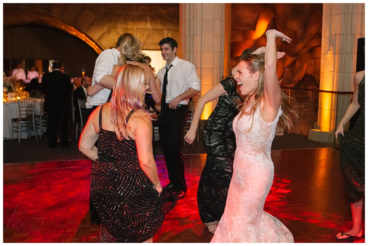 A bride and wedding guests playing a limbo during a wedding reception at Guastavinos in New York City. Dress by Ines Di Santo.