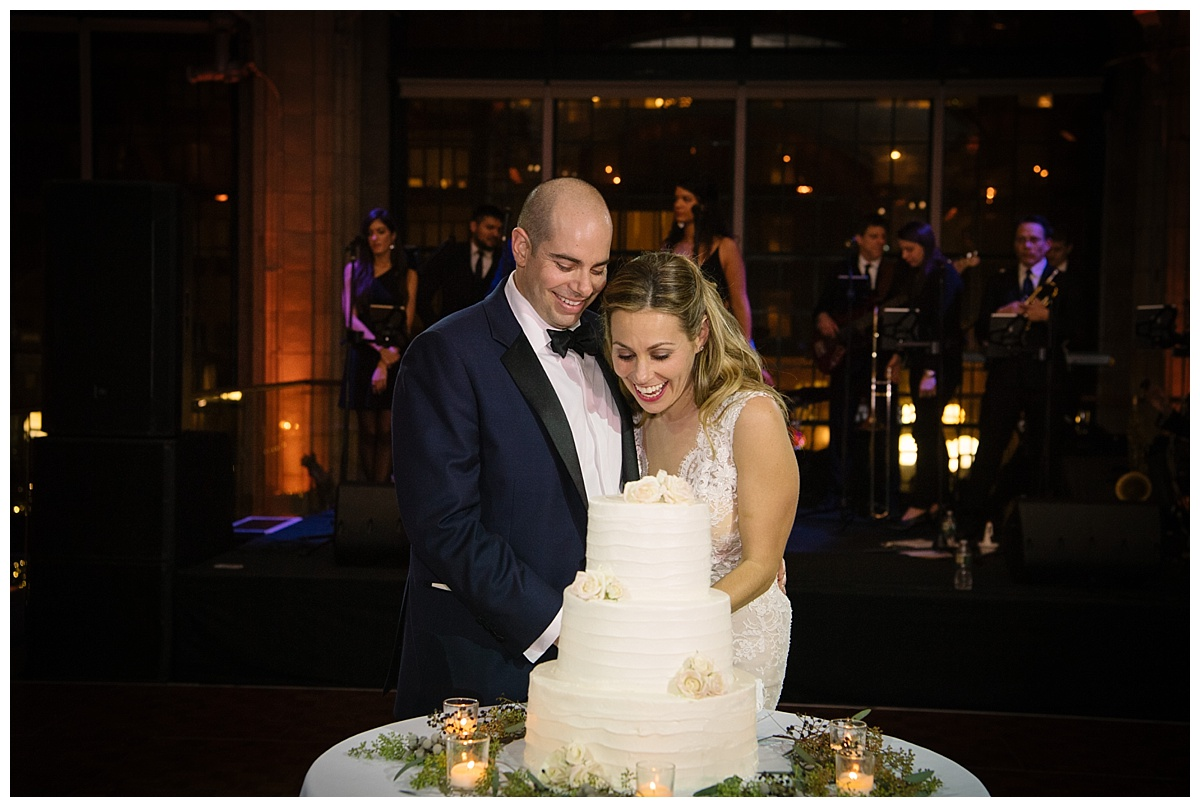 A newly wedded couple cutting their wedding cake during a wedding reception at Guastavinos in New York City.