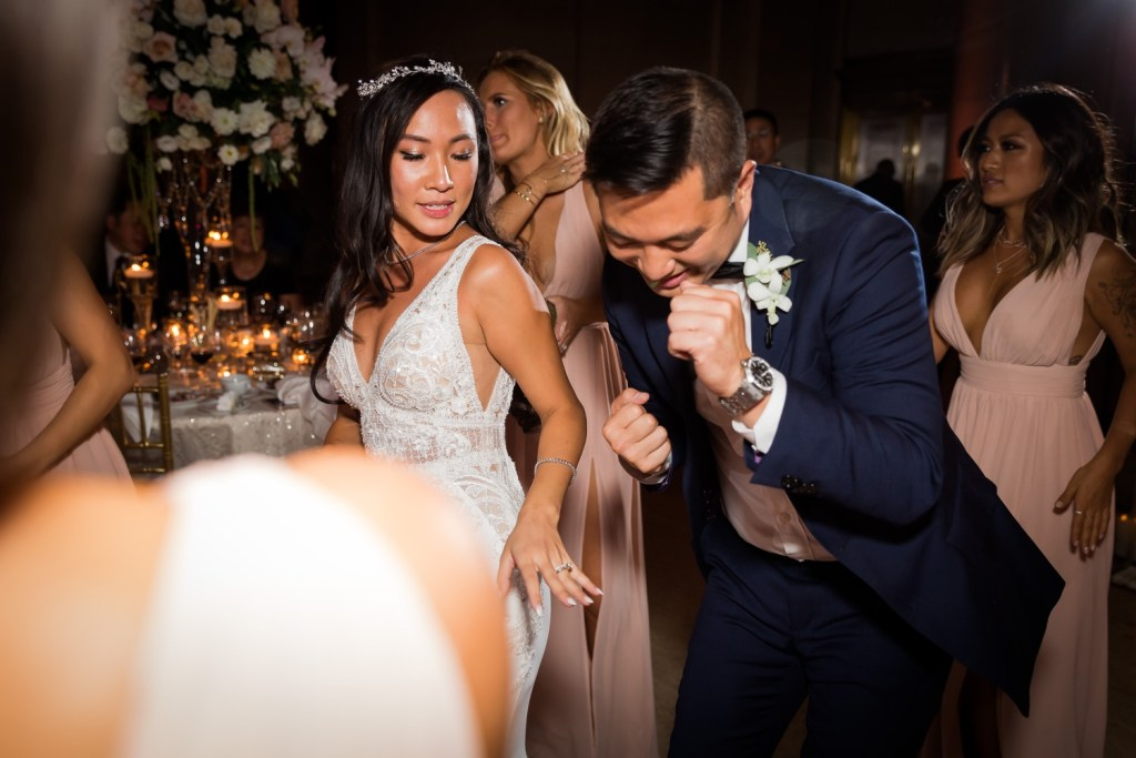 A bride dancing with a groomsman during a wedding reception at Cipriani Wall Street in New York City.