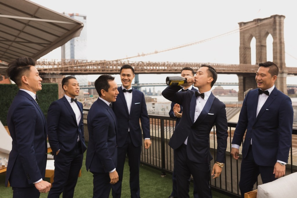 A groom drinking a bottle of champagne as a celebration in Mr. C seaport hotel on a wedding day at Cipriani Wall Street in New York City.