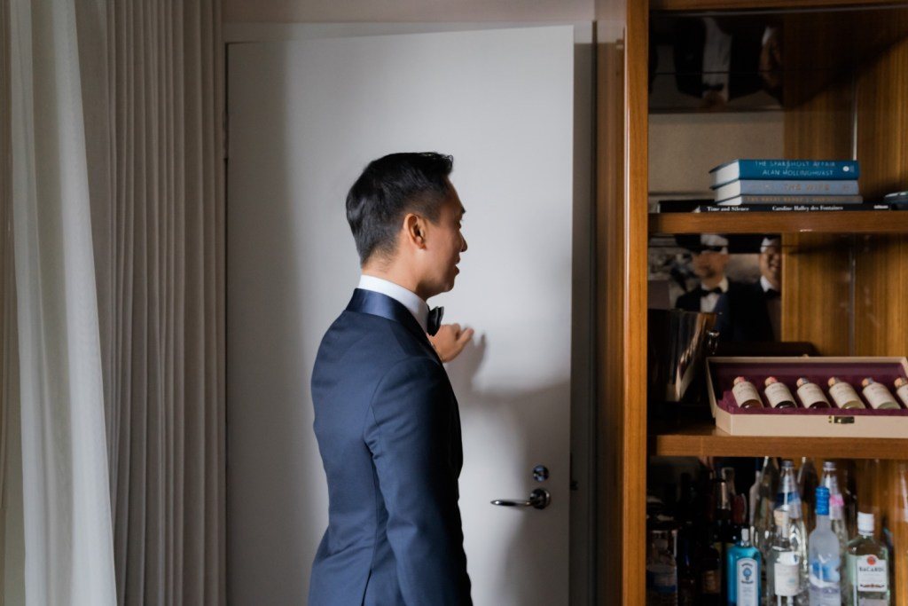 A groom knocking a door to meet his bride in a chinese dress in Mr. C Seaport Hotel on a wedding day at Cipriani Wall Street in New York City.