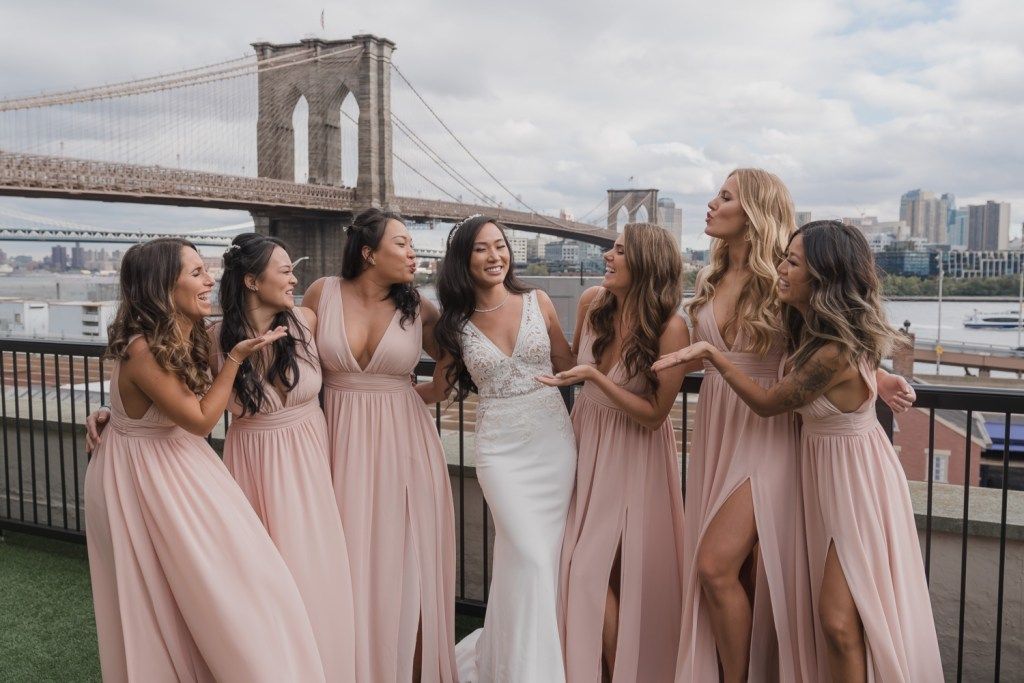 A portrait session of a bride with her wedding dress and her bridesmaids in Mr. C Seaport Hotel on a wedding day at Cipriani Wall Street in New York City. Wedding Dress by Pronovias