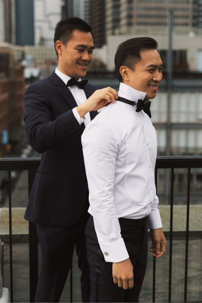 A best man helping a groom to wear a bowtie in a Mr. C Seaport Hotel on a wedding day at Cipriani Wall Street in New York City.