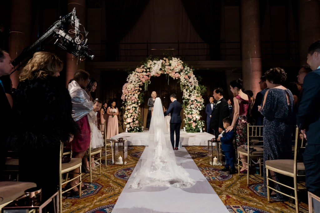 A bride and a groom entering their wedding ceremony at Cipriani Wall Street in New York City.