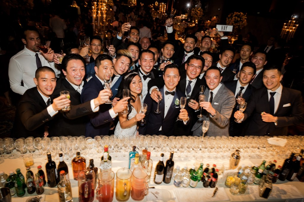 Wedding guests and a newly wedded couple posing for a group picture during a wedding reception at Cipriani Wall Street in New York City.