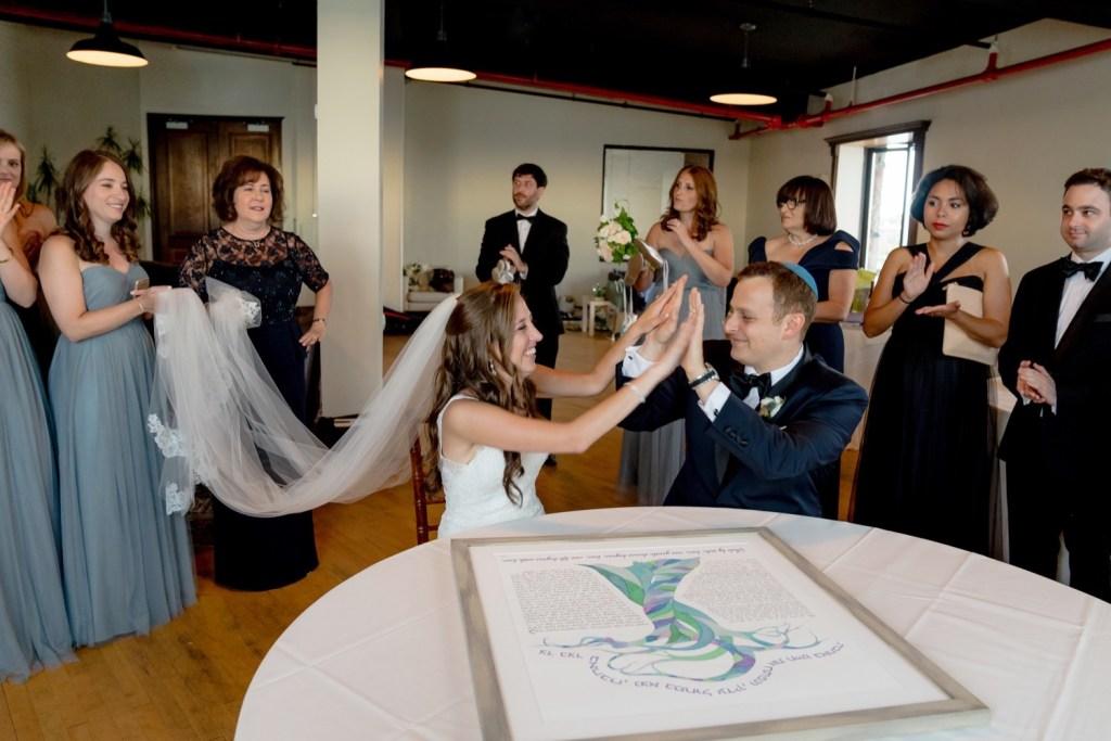 A bride and a groom signing a ketubah at Liberty Warehouse, Brooklyn New York.