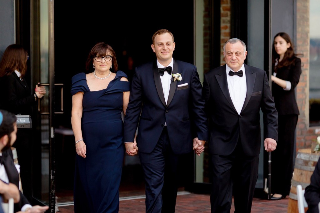 A groom and his parents walking in an aisle during a wedding ceremony at Liberty Warehouse, Brooklyn New York.