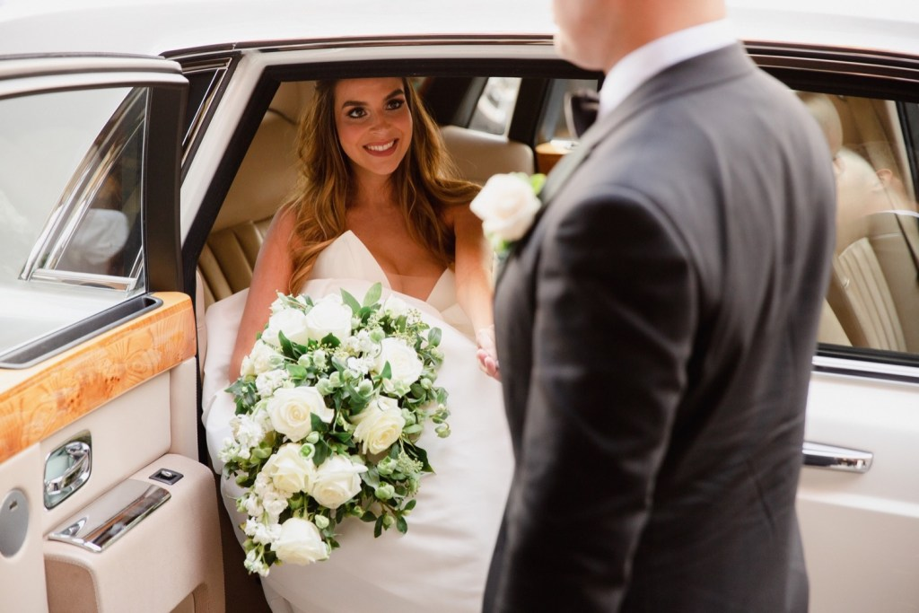 A newly wedded bride getting out a limo while holding her husband's hand.