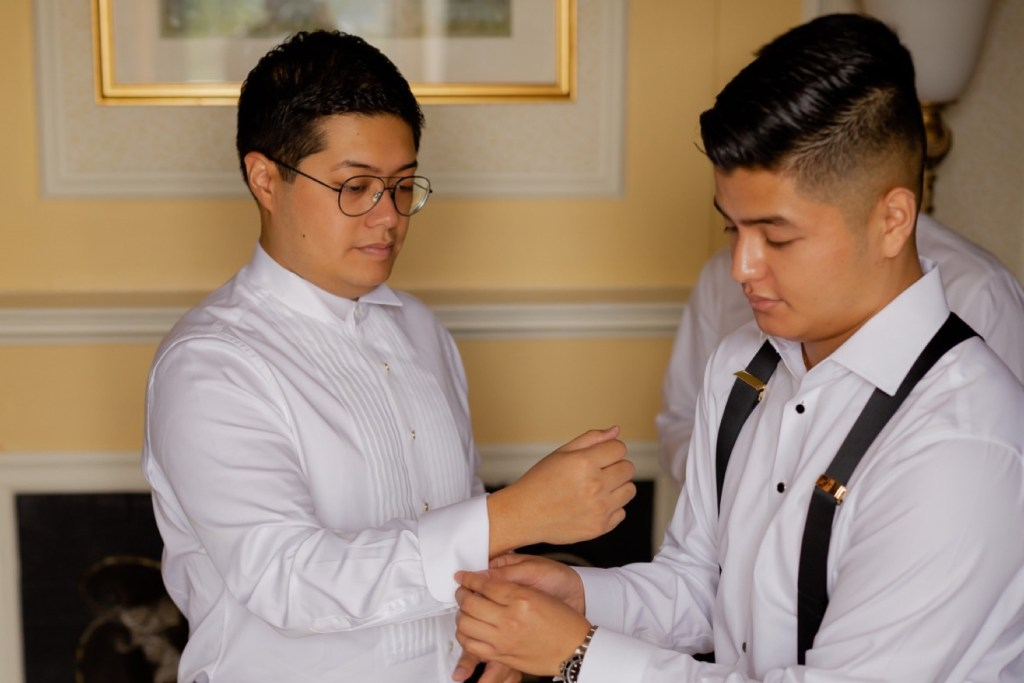 A groom getting ready with a help from his groomsmen.